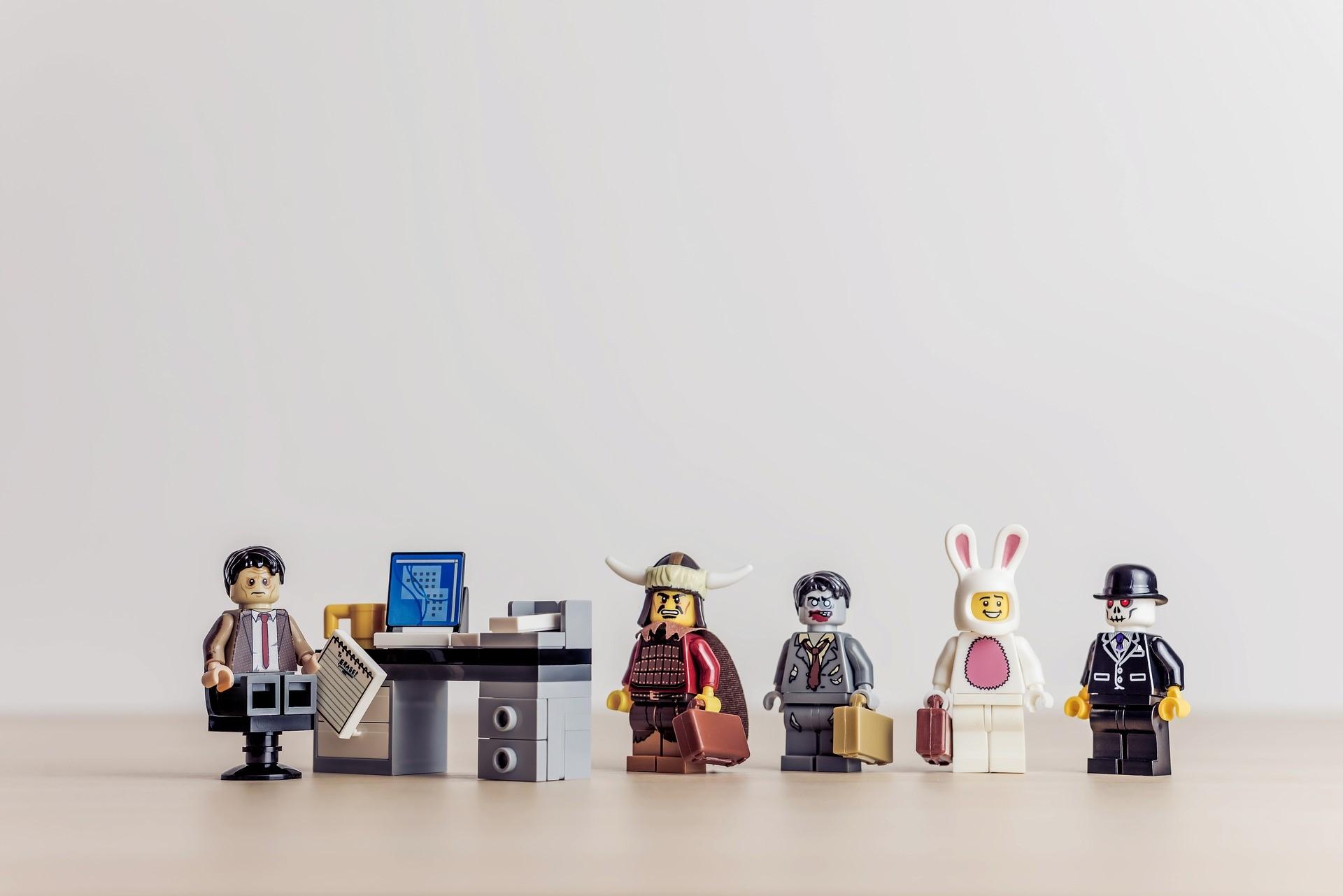 Lego Figuren: Eine vor einem Schreibtisch, die anderen in einer Reihe davor